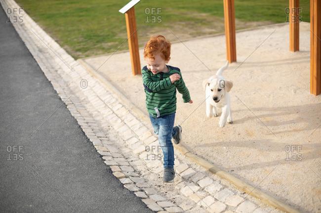 Boy running away from pet puppy