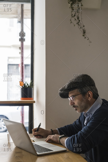 Businessman using laptop and writing notes in restaurant