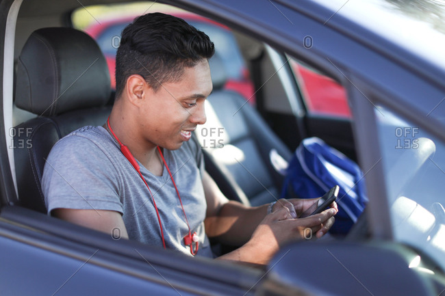 Young man sitting in car looking at smartphone