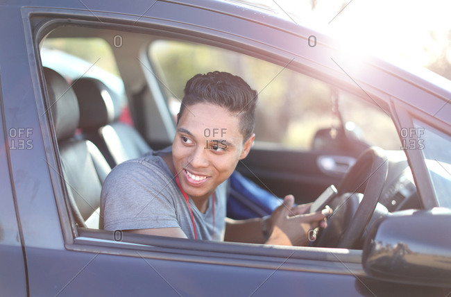 Young man sitting in car with smartphone looking out of window