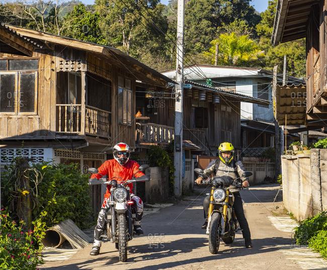 Bikers on scrambler stopping at small village, Nan, Thailand