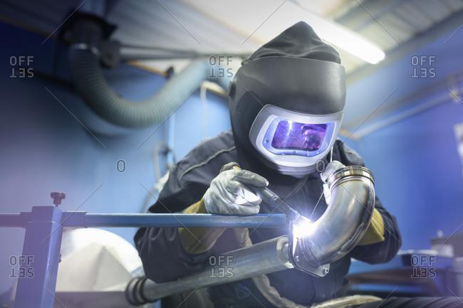 Engineer wearing mask to weld in engineering factory