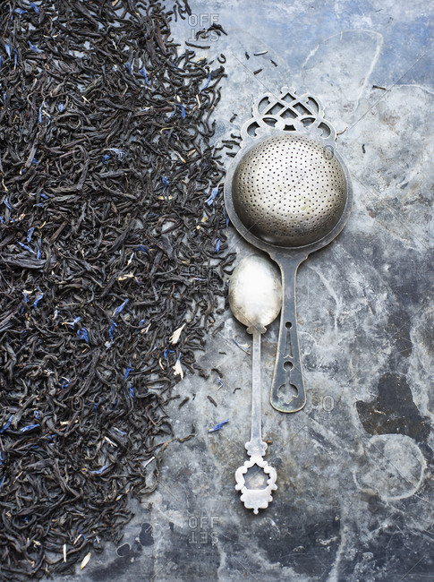 Tea leaves, tea strainer and silver spoon
