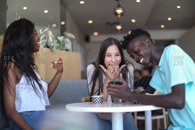 Friends using smartphone in ice cream parlor
