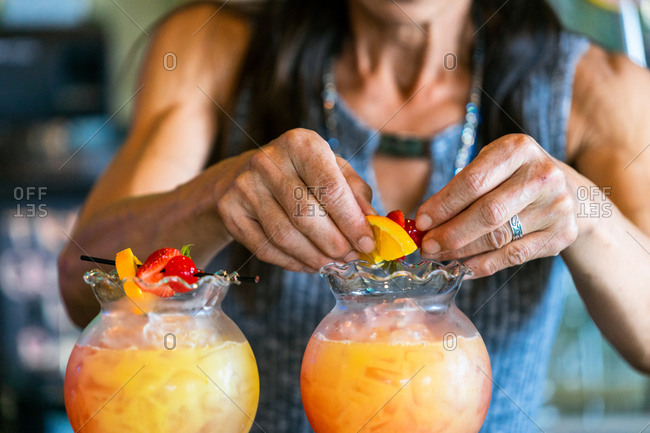 Close up of middle aged woman's hands making drinks with fruit