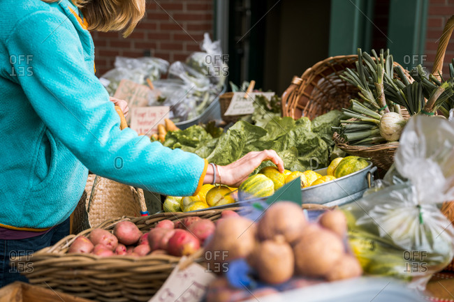 Young woman picking vegetables at farmers market