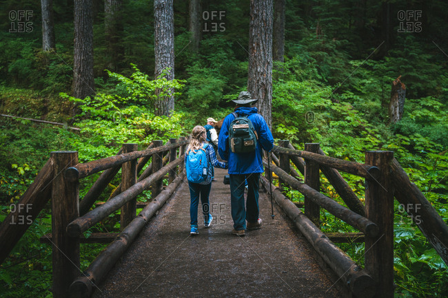 Father and daughter holding hands walking across bridge in forest