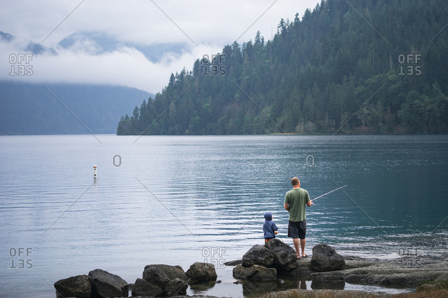 Father and son fishing at edge of scenic lake