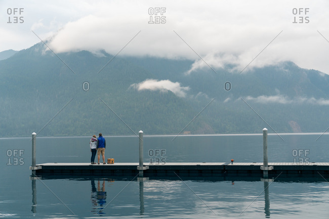 Man and woman standing on dock looking at foggy mountains