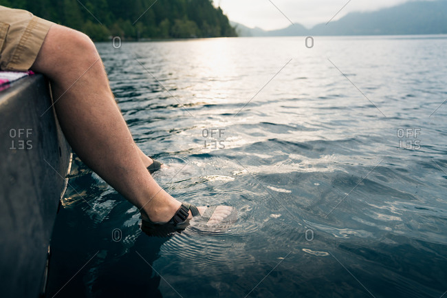 Man's feet in sandals dipped into lake