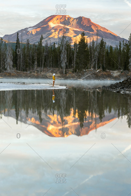 Young woman standing on edge of lake with mountain reflection