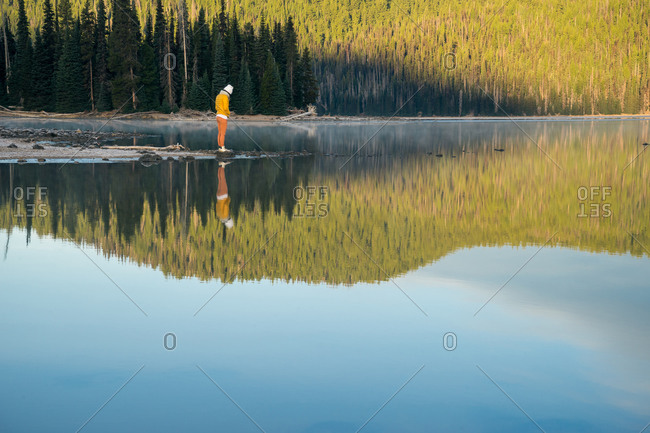 Young woman looking at reflection of trees in lake