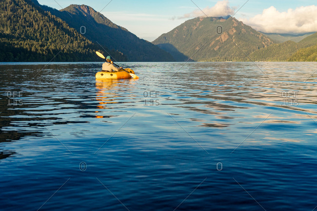 Young man paddling on lake towards mountain at sunset