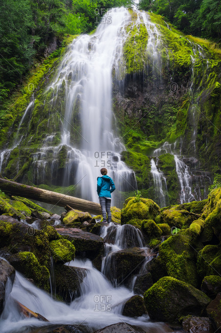 Young woman looking up at huge waterfall in forest