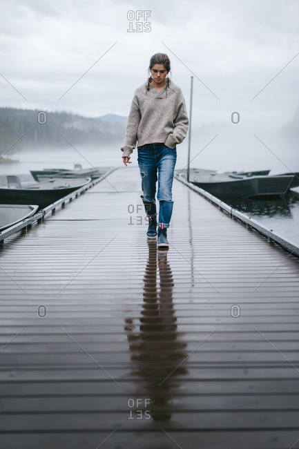 Young woman walking across as wet dock on a foggy lake