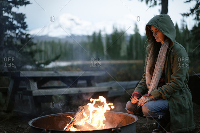 Woman crouched by campfire with hood up