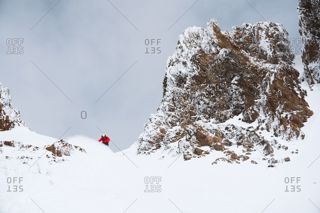 Snowboarder in red jacket making a turn in the mountains