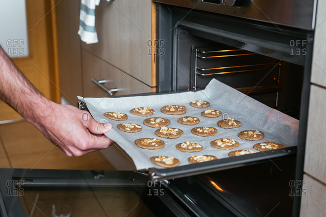 Young man putting the home-made cookies in the oven