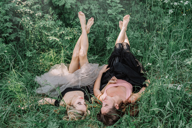 Two beautiful girls are lying in the grass