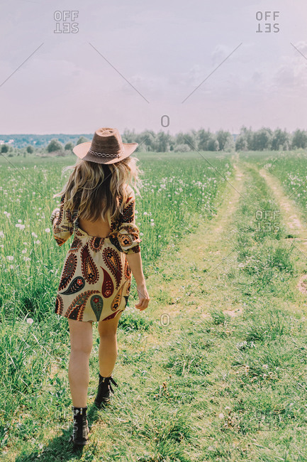 A girl in a cowboy style and a hat is walking across the field