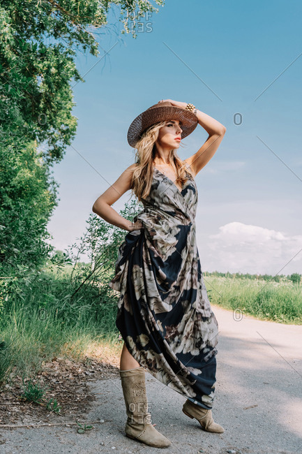 Girl in a long dress boots and hat in the field