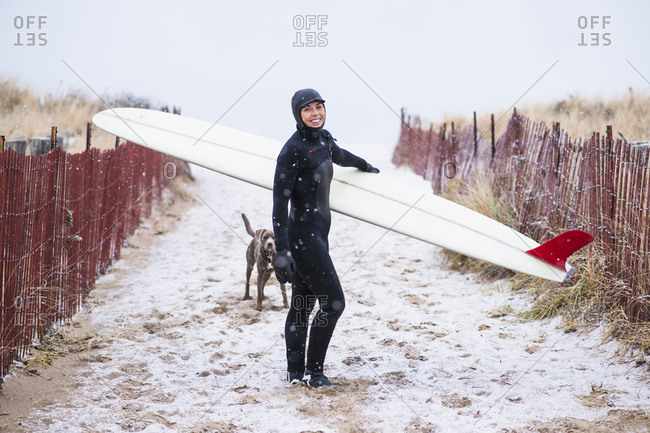 Young woman and dog going winter surfing in snow