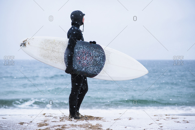 Young woman going winter surfing in snow
