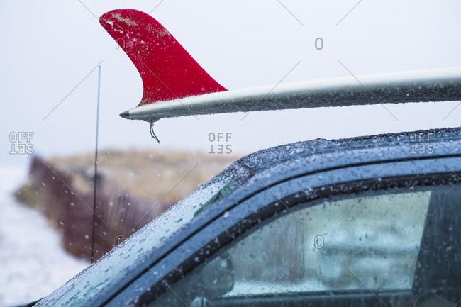 Snowy frozen surfboard on a car