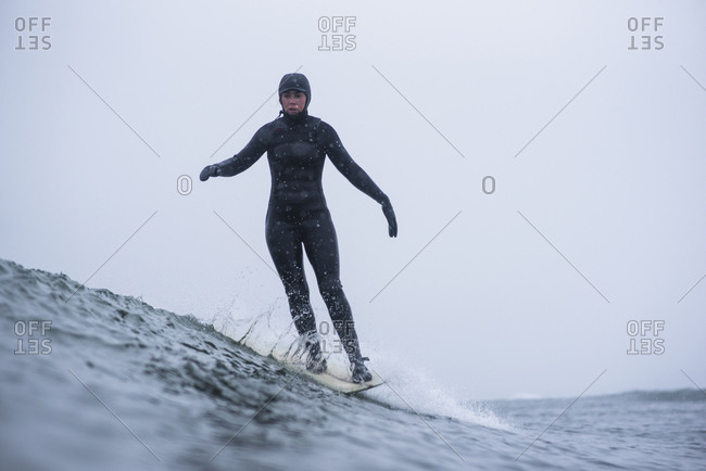Woman surfing during winter snow