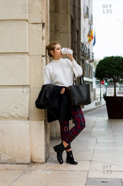 Young woman drinks coffee and looks around her on the street