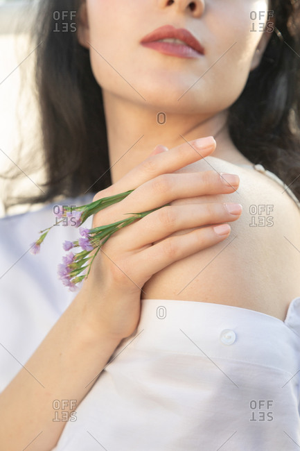 creative portrait of woman holding flowers in the sunshine