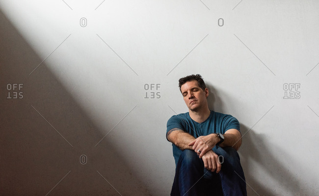 Portrait of tired man leaning against white wall with his eyes closed.