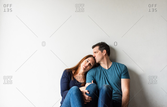 Cropped image of loving couple sitting together against a white wall.