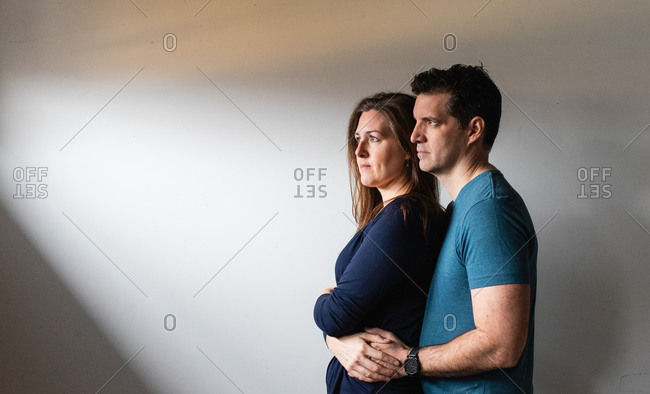 Couple standing close together in a patch of light against white wall.