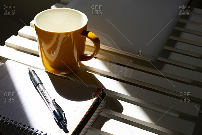 Yellow cup of coffee on a desk with a calendar and a pen.