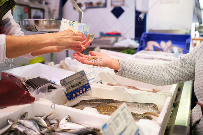 Fishmonger's hands taking money from his client