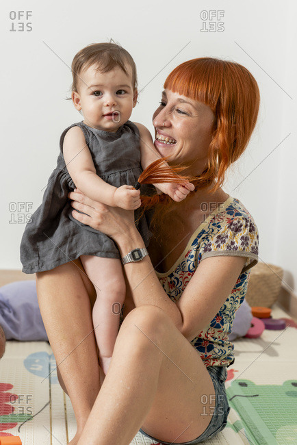 Redheaded mother having some fun and playing her baby girl daughter