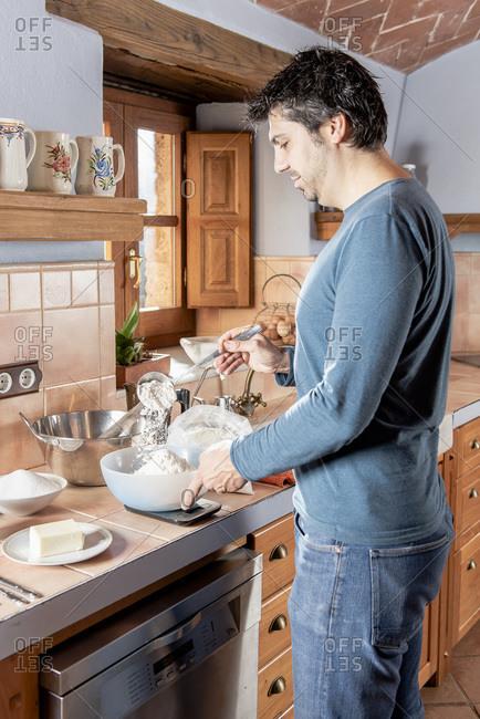 Middle aged man preparing ingredients to cook pastries.
