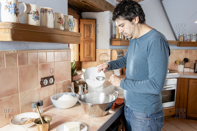 Middle aged man mixing flour, sugar and other ingredients to cook
