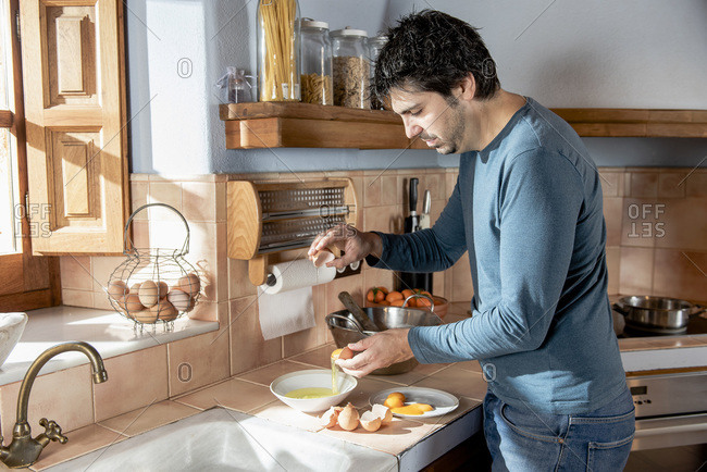 Middle aged man separating and mixing eggs to cook homemade pastry