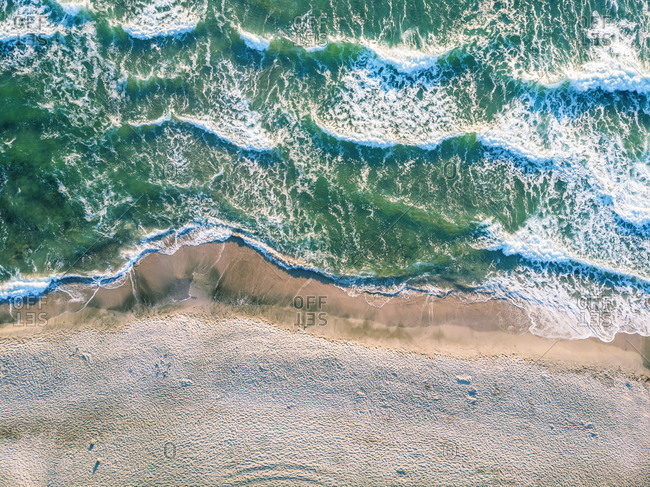Aerial view of ocean waves crashing on beach.