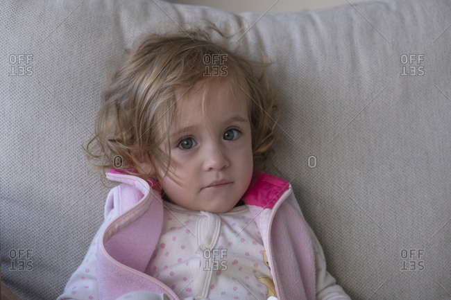 Little girl looking at the camera, on the couch in her living room.