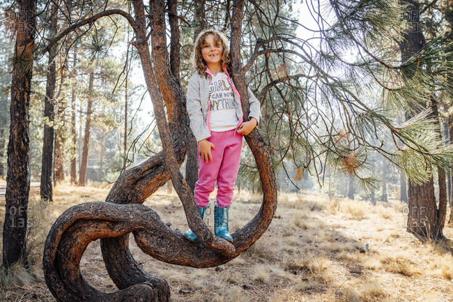 Smiling girl in sweats and rubber books standing on tree branch