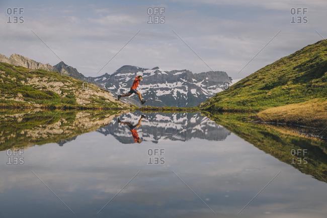 A hiker is jumping reflected in a mountain lake in Chamonix Valley.