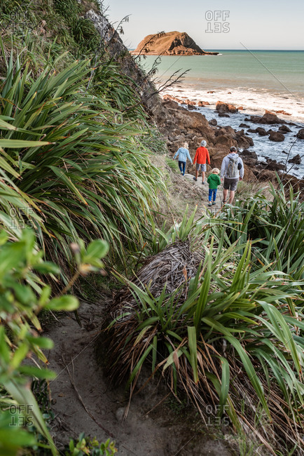 Father and children hiking near ocean in New Zealand
