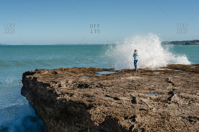 Preteen girl standing on rock with wave splashing in New Zealand