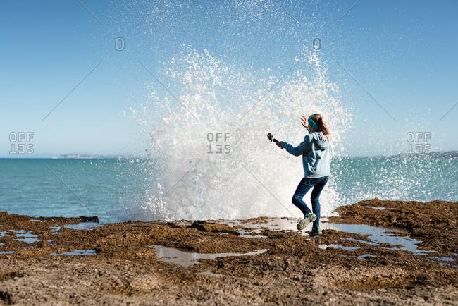 Tween startled by wave crashing over rock