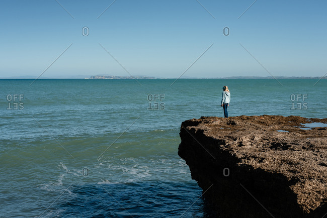 Tween girl standing on cliff overlooking ocean