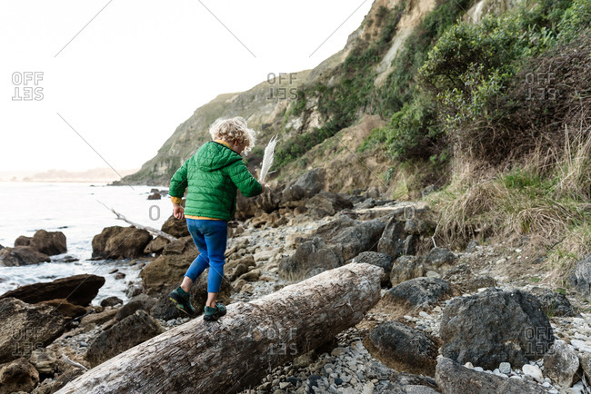 Curly haired child walking on log near ocean in New Zealand