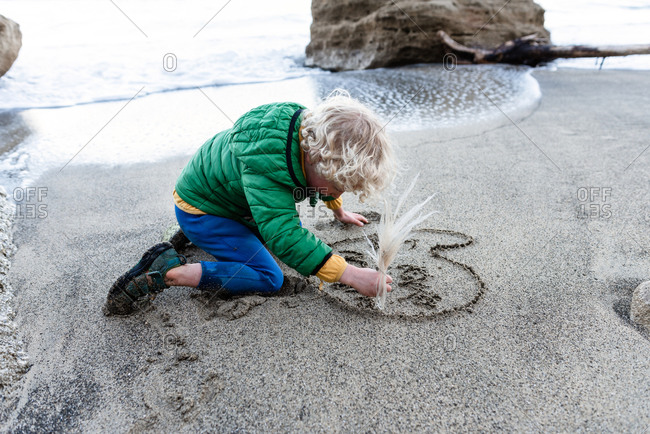Small child writing I love mum in the sand at a beach in New Zealand